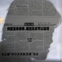 A woman's shadow falls across the glass covering a Global Times newspaper story on detained human rights lawyers that calls U.S. criticism uncomfortable but inconsequential in Beijing on Tuesday. | AP