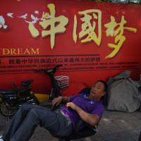 A man rests in front of a banner about the 'China Dream,' President Xi Jinping's vision for the nation's future, in Beijing on Tuesday. | AFP-JIJI