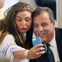 Kate Fallas takes a picture with Republican presidential candidate New Jersey Gov. Chris Christie before he spoke to a group sponsored by Americans for Peace Prosperity and Security, Wednesday in Manchester, New Hampshire. | AP