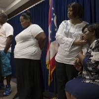 Audrey DuBose is comforted by her daughter, Terina Allen, during a news conference after murder and manslaughter charges against University of Cincinnati police officer Ray Tensing were announced for the traffic stop shooting death of her son, Samuel DuBose, Wednesday in Cincinnati. | AP
