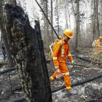 Cpl. Kevin Deng, a member of the Canadian Forces, looks for hotspots from wildfires near Montreal Lake, Saskatchewan, Thursday. | JEFF MCINTOSH / THE CANADIAN PRESS VIA AP