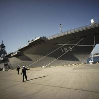 Self-Defense Forces personnel prepare to receive Indian Defense Minister Manohar Parrikar in front of the Izumo, a Japanese helicopter carrier designated as a destroyer, in Yokosuka, Kanagawa Prefecture, in March. | AP