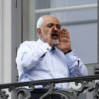 Iranian Foreign Minister Javad Zarif talks to journalists from the balcony of Palais Coburg in Vienna, the venue for nuclear the talks, on Monday. | REUTERS