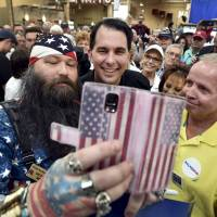 Republican presidential candidate and Wisconsin Gov. Scott Walker takes a selfie with supporters during a visit at a Harley-Davidson motorcycle dealership in Las Vegas on Tuesday. Walker criticized the recent Iran deal, saying he would 'place crippling economic sanctions' on the country if elected president.   REUTERS