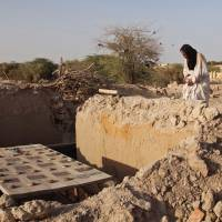 Mohamed Maouloud Ould Mohamed, caretaker of the tombs at Timbuktu's mausoleums, prays in April 2014 at a damaged tomb in Timbuktu, Mali. The 14 mausoleums in Mali's northern Timbuktu that had been destroyed by Islamic extremists years ago have been restored. | AP