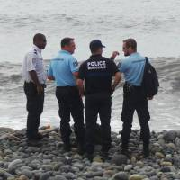 French gendarmes and police stand on the beach where a wing flap washed ashore in Saint-Andre, on the French territory of Reunion Island on Thursday. France's BEA air crash investigation agency said it was examining the debris to determine whether it came from Malaysia Airlines Flight 370.   REUTERS
