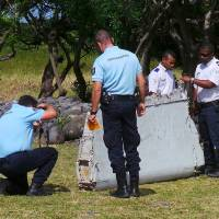 French gendarmes and police inspect a wing flap that washed ashore in Saint-Andre, Reunion Island, off the coast of Madagascar, on Thursday. France's BEA air crash investigation agency said it was examining the debris to determine whether it came from Malaysia Airlines Flight 370.   REUTERS