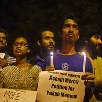 Dozens of Indian activists light candles and hold banners urging the president to stop the scheduled death penalty of 1993 Mumbai blasts accused Yakub Abdul Razak Memon, as they gather near the Indian Parliament in New Delhi Wednesday. | AP