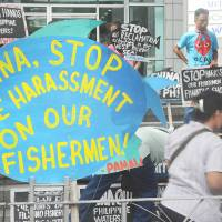 Activists hold a rally in front of the Chinese Consulate in Manila's financial district on July 3 to protest Beijing's reclamation work in the South China Sea, which the protesters say has displaced Filipino fishermen.   AFP-JIJI