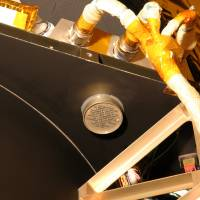 This undated photo provided by Johns Hopkins University Applied Physics Laboratory via NASA shows an aluminum canister containing the ashes of Clyde Tombaugh, the American astronomer who discovered Pluto in 1930, attached to NASA's New Horizons spacecraft. On Tuesday, July 14, 2015, the spacecraft is scheduled to pass within 7,800 miles of Pluto, which he discovered 85 years ago. | JOHNS HOPKINS UNIVERSITY APPLIED PHYSICS LABORATORY VIA AP
