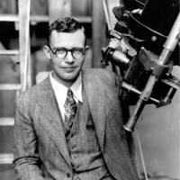 In this 1931 file photo, Clyde Tombaugh poses with the telescope through which he discovered Pluto at the Lowell Observatory on Observatory Hill in Flagstaff, Arizona. | AP