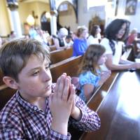 A boy and his family pray during Mass at Saint Joseph Catholic Church in Detroit on Saturday, ahead of the unveiling of a controversial goat-headed Baphomet sculpture in the city. | AP