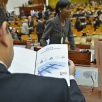 A delegate from the International Seabed Authority reads material distributed by a nongovernment organization ahead of a meeting of the U.N. body in Kingston, Jamaica, on July 14. | AP