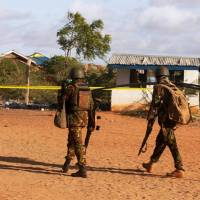 Kenya Defense Forces soldiers walk near the scene of an overnight attack on a residential complex in Mandera town at the Kenya-Somalia border Tuesday. Somalia's al-Shabaab Islamist group said on Tuesday it was behind a gun attack in Mandera, a raid it said was part of its campaign against Kenya. | REUTERS