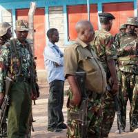 Kenya Defense Forces soldiers and policemen gather at the scene of an overnight attack on a residential complex in Soko Mbuzi village of Mandera town at the Kenya-Somalia border Tuesday. | REUTERS