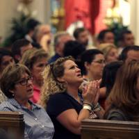 Parishioners sing a hymn during a prayer service for the victims of The Grand 16 theater shooting at the Cathedral of St. John the Evangelist, in Lafayette, Louisiana, Sunday. John Russell Houser stood up about 20 minutes into Thursday night's showing of 'Trainwreck' and fired on the audience with a semi-automatic handgun that, according to reports he was able to buy despite a history of mental problems because he was never involuntarily committed.   AP