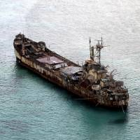 Filipino soldiers wave from the Philippine navy's dilapidated Sierra Madre in May. The World War II-era ship is grounded on Ayungin Shoal, also known as the Second Thomas Shoal, in the Spratly Islands. | REUTERS