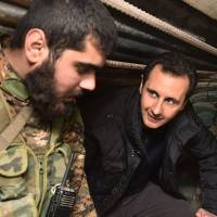 Syrian President Bashar al-Assad speaks with troops during a visit to the eastern Damascus district of Jobar on Dec. 31.   AFP-JIJI