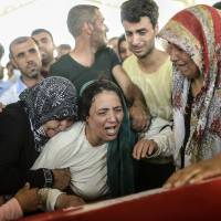 The mother of a suicide bombing victim in the Turkish border town of Suruc cries next to the coffin of her son during a funeral in Gaziantep on Tuesday.   AFP-JIJI