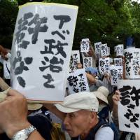 Protesters hold placards during an anti-government rally outside the Diet in Tokyo on Saturday. Controversial security bills that opponents say will undermine 70 years of pacifism and could see Japanese troops fighting abroad for the first time since World War II were rammed through the powerful Lower House by the ruling bloc Thursday. | AFP-JIJI