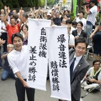 Lawyers for plaintiffs seeking the suspension of flights at Atsugi air base in Kanagawa Prefecture hold up a banner Thursday in front of the Tokyo High Court. | KYODO