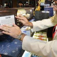 An employee at a duty-free store in Narita International Airport places a sticker July 3 warning travelers not to exceed carry-on restrictions. | KYODO