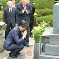 Prime Minister Shinzo Abe visits the grave of his grandfather, Prime Minister Nobusuke Kishi, last August in the town of Tabuse, Yamaguchi Prefecture. | KYODO