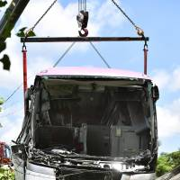 A tour bus that struck a dump truck and went off an expressway in Yokkaichi, Mie Prefecture, is lifted by crane from a tea plantation on Tuesday. | KYODO