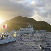 A Chinese surveillance ship cruises past a Japanese fishing boat chartered by a political group near the Senkaku Islands in July 2013. | KYODO