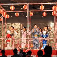 Enka singer Yuki Tokunaga (third from left) takes the stage with other performers and SoftBank Pepper humanoid robots Friday evening at a summer festival in Tokyo's Shibuya district.   YOSHIAKI MIURA