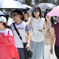 Pedestrians try to keep cool walking in Tokyo's Ginza district on Monday. | KYODO
