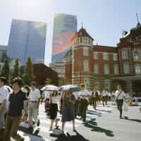 Pedestrians make their way from JR Tokyo Station in the summer heat on Tuesday morning. | KYODO