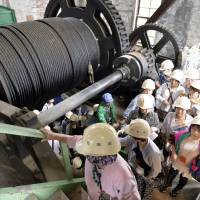 Tourists pass a winch at the Manda Pit of the Miike Coal Mine in Arao, Kumamoto Prefecture, on Monday. The coal mine is one of 23 industrial sites from the Meiji Era that have been added to the UNESCO World Cultural Heritage list. | KYODO