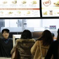 An employee raises her hand to serve customers at a McDonald's restaurant in Tokyo on Feb. 3. | BLOOMBERG