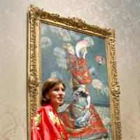 Sue Danielson, visiting from Kentucky, poses with Monet's 'La Japonaise' during the Cheers to Malcolm! event at the Museum of Fine Arts in Boston on June 23. The museum had kimonos for people to try on and pose as Camille Monet did in the painting. The Museum of Fine Arts Boston  eventually canceled the 'Kimono Wednesdays' events after protesters decried the event as racist.  | AP / JOHN BLANDING / BOSTON GLOBE