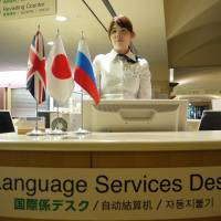 Maya McDonald tends the international desk at St. Luke's International Hospital in Tokyo's Chuo Ward. The facility  handles 1,800 to 2,000 visits by non-Japanese patients every month. | TOMOKO OTAKE