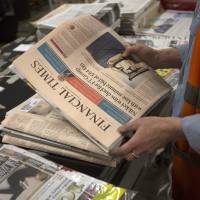 Copies of the Financial Times are prepared for delivery by an employee on Friday. | BLOOMBERG