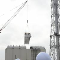 The cover shrouding the reactor 1 building at the Fukushima No. 1 nuclear plant is dismantled Tuesday as members of a Fukushima Prefectural Government safety council watch. | KYODO