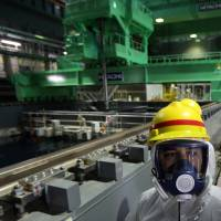 A member of the media walks in front of a fuel handling machine at the spent fuel pool inside the building housing reactor 4 at the Fukushima No. 1 nuclear plant in November 2013. | BLOOMBERG