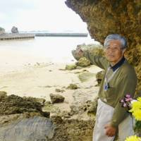 Yoshitami Oshiro, a member of Nago Municipal Assembly, stands besides a grave of his ancestors in April and points to a coastal area in Nago where the Futenma replacement base is planned.   KYODO