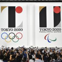 The official emblem of the Tokyo 2020 Olympic (left) and Paralympic Games is unveiled by the Tokyo 2020 Organizing Committee to a large crowed gathered in front of the Tokyo Metropolitan Government office on Friday night. | KYODO
