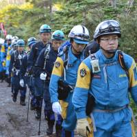 An advance team of Nagano police officers and firefighters enters the Mount Ontake area from the Nagano Prefecture side on Sunday ahead of resuming the search for bodies later this month that remain buried following the volcano's deadly eruption last September. | KYODO
