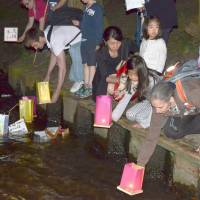 Participants in Potsdam, Germany, on Saturday recall the victims of the U.S. atomic bombings of Hiroshima and Nagasaki almost 70 years ago. They launched paper lanterns onto water. | KYODO