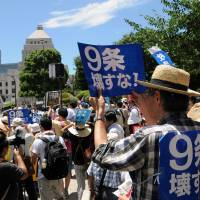 People rally in front of the Diet on Wednesday, as the ruling bloc bulldozed security bills through at a special committee of the Lower House. | SATOKO KAWASAKI