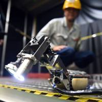 A Toshiba engineer watches a small robot with two CCD cameras, developed by Toshiba Corp. and the International Research Institute for Nuclear Decommissioning, in a demonstration at a Toshiba factory in Yokohama on Tuesday. | AFP-JIJI