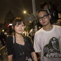 Touri Ise (left), head of the design team for the pro-democracy youth group SEALDs, and fellow member Yoshimasa Ushida pose for a photo during a recent protest over the security bills in front of the Diet. | CHIAKI UEDA