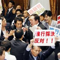 Special security bill Yasukazu Hamada committee chairman (center) is surrounded by opposition politicians shouting and waving placards in protest of security bill legislation that passed through a House of Representatives panel Wednesday morning. | KYODO