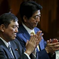 Japan's Prime Minister Shinzo Abe and minister in charge of reviving local economies Shigeru Ishiba applaud after the government-proposed security-related legislation passes in the Lower House during the plenary session of the parliament in Tokyo on Thursday.   REUTERS