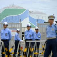 Police and security guards stand in front of the Sendai nuclear plant in Satsumasendai, Kagoshima Prefecture, on Tuesday. | KYODO