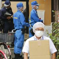 An investigation team from the Shizuoka Prefectural police department remove evidence on Wednesday from the home of Haruo Hayashizaki in Suginami Ward, Tokyo. Hayashizaki lit himself on fire Tuesday morning while aboard the Tokaido Shinkansen bound for Osaka.  | KYODO